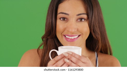 Close up of cheerful Latina female holding coffee mug on green screen