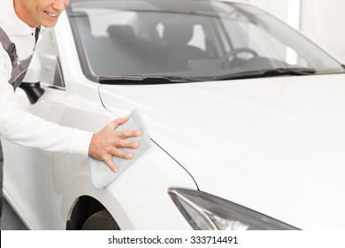 Close up of cheerful male mechanic cleaning a white car with cloth. The man is standing in uniform and smiling