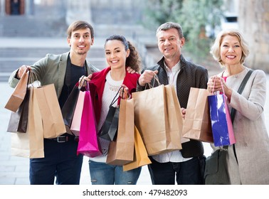 Close up of cheerful positive smiling tourists with purchases on European city street