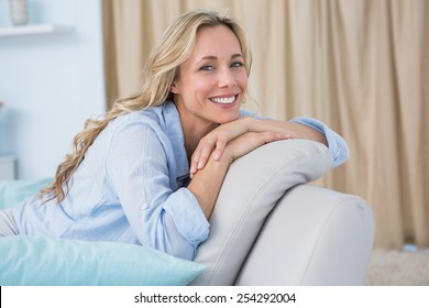 Close up of cheerful pretty blonde sitting on couch at home in the living room