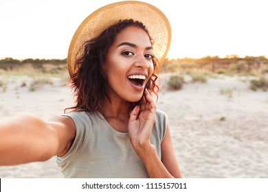 Close up of cheerful young african girl in summer hat taking a selfie at the beach
