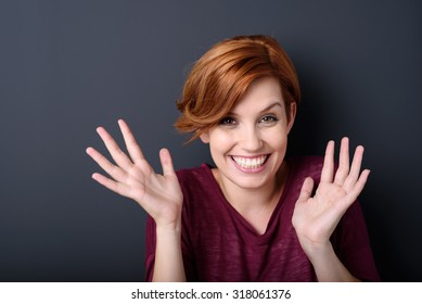 Close up Cheerful Young Blond Woman Smiling at the Camera with Open Hands Against Gray Wall Background In the Studio.