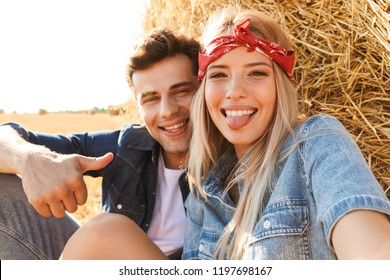 Close up of a cheerful young couple sitting at the wheat field, taking a selfie