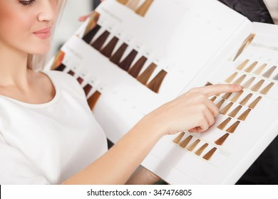 Close up of cheerful young woman sitting at hairdressing salon. She is sitting and pointing finger at pallet of hair color. The lady is smiling