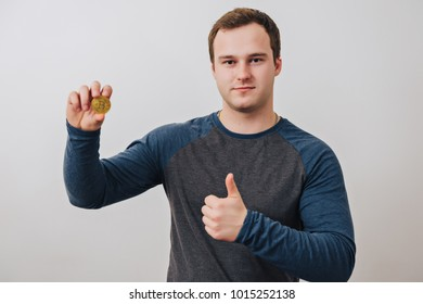 Close up of a cheery businessman holding bitcoin and showing thumb up isolated over white background.
