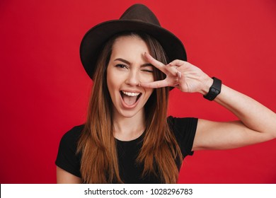 Close up of a cheery stylish girl wearing hat showing peace gesture isolated over pink background