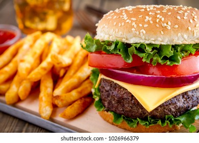 Close up of cheese burger with onions, lettuce, tomato on a sesame seed bun with seasoned french fries and ketchup with glass of iced tea in background