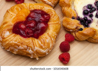 Close up of cheese danishes puff pastry with cherry jam, blackberries and fresh raspberries