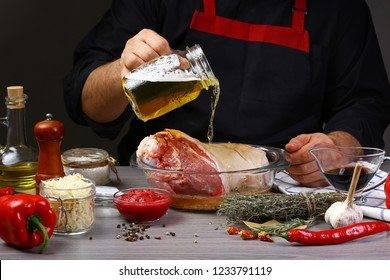 Close up of a chef hands preparing pork knuckle. Cook preparing delicious pork knuckle with the addition of beer. The concept of Bavarian cooking recipe.