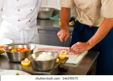 Close up of chefs in a commercial restaurant or hotel kitchen working, they are preparing an fish fillet and vegetables