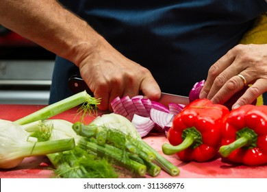 close up of a chef's hands slicing fresh vegetables in a restaurant