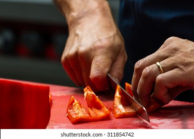 close up of a chefs hands slicing sweet bell peppers on a red cutting board