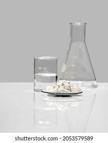 Close up chemical ingredient on white laboratory table. Calcium carbonate Chip in Chemical Watch Glass place next to beaker with alcohol and Erlenmeyer flask. Side View