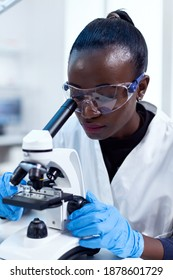 Close up of chemist of african ethnicity doing sample analysis looking through microscope. Black healthcare scientist in biochemistry laboratory wearing sterile equipment.