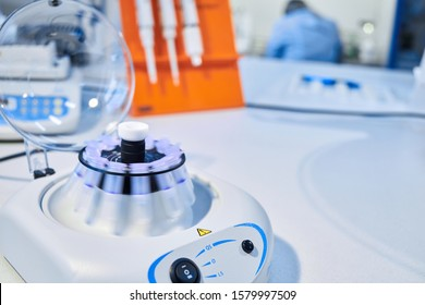 Close up of a chemist using a centrifuge rotor in lab  for medical and scientific research. Close-up of opened laboratory centrifuge with samples inside of rotating units used for separating liquids.