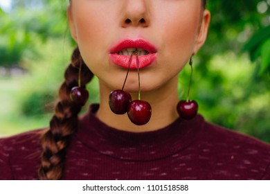 Close up cherry in mouth of a young woman