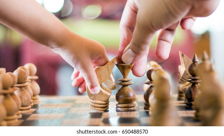 close up chess game move shot with kid and parent hand