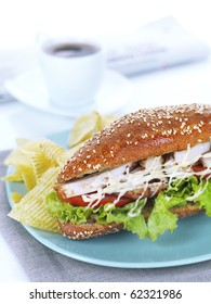a close up of a chicken breast submarine with sesame  whole wheat bread,roasted chicken breast,tomatoes,served with potato chips .There is also a white cup of an espresso coffee and a newspaper on