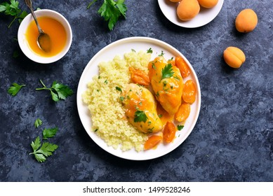 Close up of chicken breasts in apricot sauce and couscous on white plate over blue stone background. Tasty healthy stewed chicken meat with garnish. Top view, flat lay