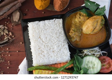 close up of a chicken curry, is a food made from chicken soaked with herb and spices sauce, presenting with rise, bean sprouts, tomato, cucumber, carot and long beans as vegetable on a wooden table