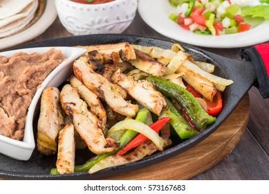 Close up of chicken fajitas on cast iron.