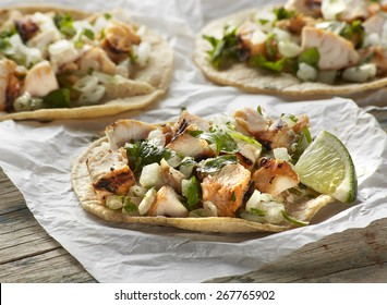 Close up of chicken street taco on wood
