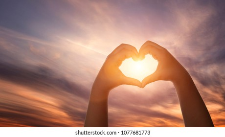 Close up of child hands formig heart shape over beautiful sky background with copy space