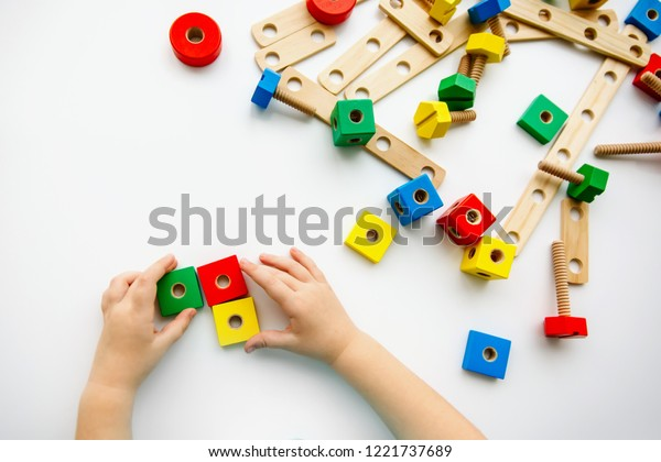 Close up of child hands playing with colorful wooden bricks at the table. Toddler having fun and building out of bright constructor bricks. Early learning. Top view. Flat lay.