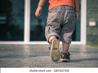 close up of child legs walking away from camera toward house door