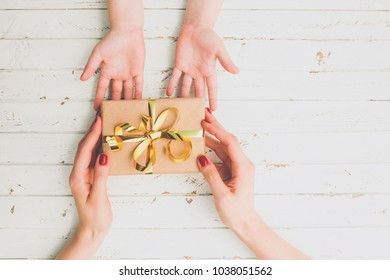 Close up of child and mother hands with gift box over wood background