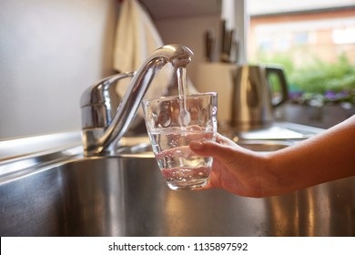 Close up of children hands, pouring glass of fresh water from tap in kitchen