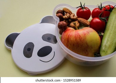 Close up of children's lunch box shaped panda head with vegetarian food: vegetables, fruits, nuts. With space for text, on a light yellow background. Concept of healthy food, snack for children