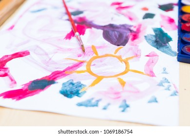 Close up of children's painting tools (paint palette, brush and paper) and child painting. Preschooler toys.
