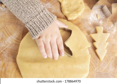 Close up of a child's hand cutting out Christmas biscuits
