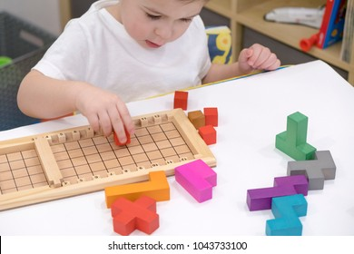 Close up of child's hands playing with colorful wooden bricks at the table.