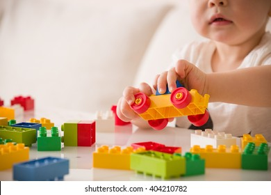 Close up of child's hands playing with colorful plastic bricks at the table. Toddler having fun and building out of bright constructor bricks. Early learning. Developing toys