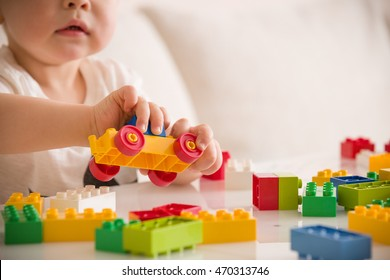 Close up of child's hands playing with colorful plastic bricks at the table. Toddler having fun and building out of bright constructor bricks. Early learning.  stripe background. Developing toys