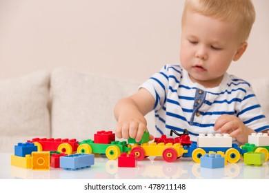 Gros plan sur les mains d'un enfant jouant avec des briques en plastique colorées à la table. Enfant s'amusant et construisant à partir de briques de construction lumineuses. Apprentissage précoce.   Développement de jouets