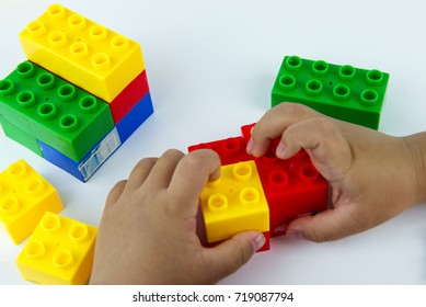 Close up of child's hands playing with colorful plastic bricks at the table. Toddler having fun and building out of bright constructor bricks. Early leaning. White background. Developing toys.