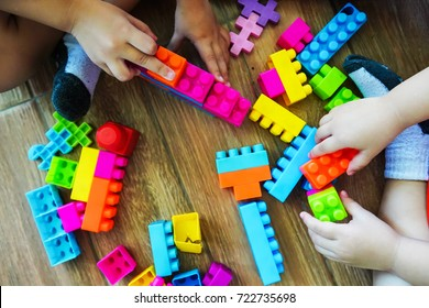 Close up of child's hands playing with colorful plastic bricks on the tile floor. Early learning. stripe background. Developing toys