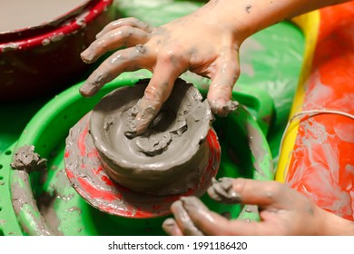 Close up childs hands works on a potter's wheel, learns to work with clay.