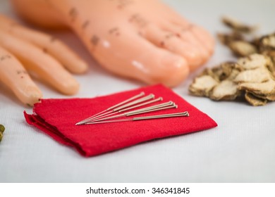 close up Chinese acupuncture needles on red cloth with meridian hand foot model with herb