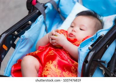 Close up of Chinese baby receiving orange, Chinese traditional in Chinese new year for Lucky, from parent in perambulator baby stroller.