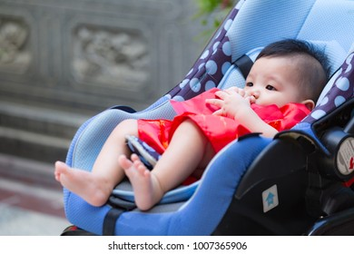 Close up of Chinese baby receiving reward, Chinese traditional in Chinese new year, from parent in perambulator baby stroller.
