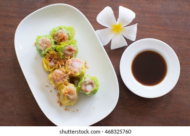 close up chinese steamed dumpling on white dish with Chinese black vinegar