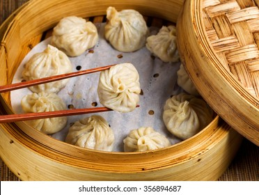 Close up of Chinese steamed dumplings, selective focus on piece held in chopsticks, being taken out of bamboo steamer with rustic wood in background.