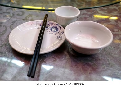 Close up of chinese style table setting with tea cup,bowl and plate with chopsticks on top on the revolving dining table in the restaurant