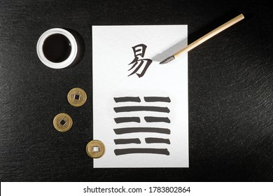 """Close up of an I Ching arrangement on slate. With chinese ideograph. Translation : """"After Completition"""". Written with a chinese ink brush on rice paper."""