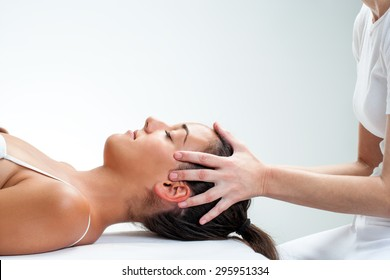 Close up of chiropractor doing healing osteopathic treatment on woman.Hands on head.