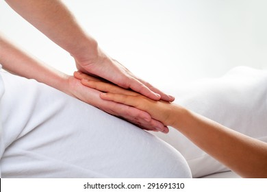 Close up of chiropractor doing reiki treatment on girls hand.